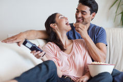 Playful couple watching TV while eating popcorn Stock Images