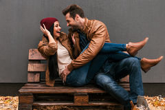 Playful couple. Playful young loving couple having fun together while sitting on the wooden pallet together with grey wall in the background and fallen leaves royalty free stock image