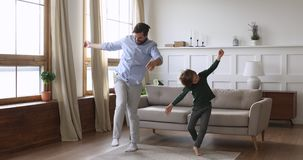 Playful crazy daddy and cute kid son having fun dancing