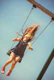 Playful crazy girl on swing. Craziness and freedom. Young summer girl playing on swing-set outdoor. Crazy playful child swinging very high to touch the sky royalty free stock photography