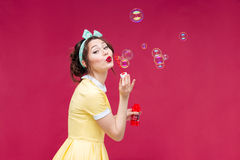 Playful cute pinup girl in yellow dress blowing soap bubbles Royalty Free Stock Image