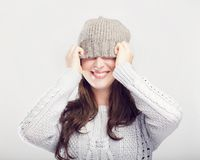 Playful cute winter girl covers eyes with hat Royalty Free Stock Photography