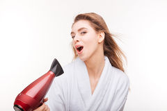 Playful cute woman singing and drying her hair with dryer Royalty Free Stock Images
