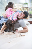 Playful daughters on top of father at home Stock Image