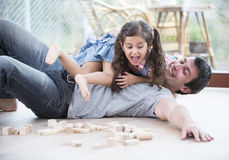 Playful daughters on top of father at home Royalty Free Stock Photo