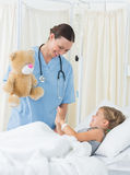 Playful doctor entertaining sick girl Royalty Free Stock Image