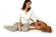 Playful Dog. Woman and her Golden Retriever dog on white background and isolated. Natural shadow still there. Woman petting her dogs tummy royalty free stock photo
