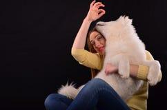 Playful dog. Beautiful girl with young, playful Siberian samojed dog posing in studio Royalty Free Stock Photography