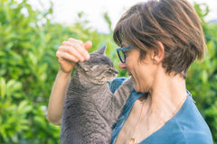 Playful domestic cat held and cuddled by smiling woman with eyeglasses. Outdoor setting in green home garden. Shallow depth of fie Royalty Free Stock Images
