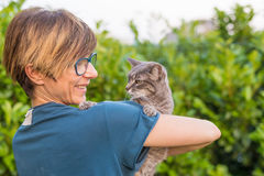 Playful domestic cat held and cuddled by smiling woman with eyeglasses. Outdoor setting in green home garden. Shallow depth of fie Stock Images
