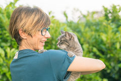 Playful domestic cat held and cuddled by smiling woman with eyeglasses. Outdoor setting in green home garden. Shallow depth of fie Stock Image