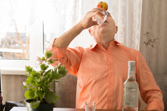 Playful Drinking Elderly with Apple on Forehead Stock Photo