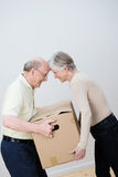 Playful elderly couple moving house. Bumping foreheads as they both try to carry the same cardboard carton royalty free stock photo