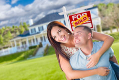 Playful Excited Military Couple In Front of Home with Sold Sign Stock Images