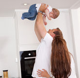 Playful Family. Happy playful family at home, mother and father throwing son in the air Royalty Free Stock Photography
