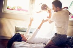 Playful family in bed together. Happy smiling family in bed. Parents playing with their daughter Stock Photography