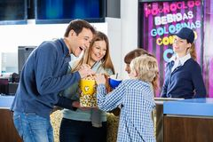 Playful Family Enjoying Snacks At Cinema. Playful family of four enjoying snacks while female worker standing at cinema concession stand Stock Photography