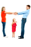 Playful family of father, mother and daughter. Playful parents holding hands while cute daughter keenly watches them Stock Image