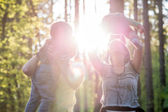 Playful Family in Forest with Bright Sun Behind stock photography