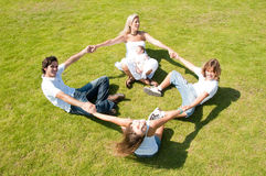 Playful family on grass. Family enjoying together on grass holding hands, forming circle Stock Photography