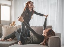Playful family having fun at home. I believe I can fly. Full length portrait of small smiling girl and her amused mother are lying on sofa with their fingers royalty free stock photos