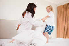 Playful family having pillow fight. In a bedroom Royalty Free Stock Photo