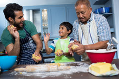 Playful family holding dough while preparing food. In kitchen at home Royalty Free Stock Image