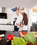 Playful Family in Kitchen. Happy playful family in kitchen - father mother and toddler son Stock Photos
