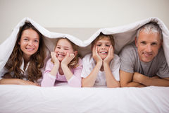 Playful family lying under a duvet Stock Images