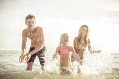 Playful family. Mom , dad. and daughter playing on the beach Royalty Free Stock Photography
