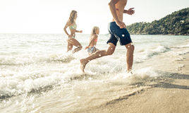 Playful family. Mom , dad. and daughter playing on the beach Royalty Free Stock Photos