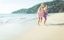 Playful family. Mom and daughter playing on the beach Royalty Free Stock Photography
