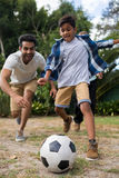 Playful family playing soccer on field. In yard Stock Photo