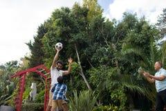 Playful family playing soccer at yard. Playful family playing soccer against plant at yard Stock Photo