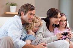Playful family playing video games together. In a living room royalty free stock photo
