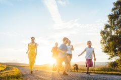 Playful family running and playing on a path in summer landscape stock images