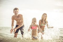 Playful family spraying water and having fun Stock Images