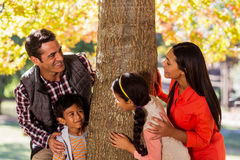 Playful family standing by tree. Playful happy family standing by tree at park Royalty Free Stock Photo