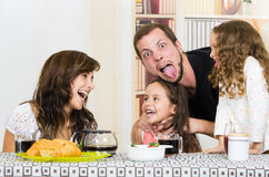 Playful family with two girls eating breakfast Stock Photography
