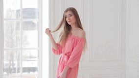 Playful fashion model in pink summer dress posing near window in studio stock video footage