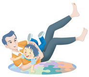 Playful father. Father and son wrestle on a jigsaw puzzle mat Stock Photo
