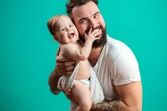 Playful father carrying his smiling infant child on neck over blue background royalty free stock photography