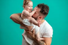 Playful father carrying his smiling infant child on neck over blue background. Playful father carrying his smiling infant child on hands and playing with her in Royalty Free Stock Image