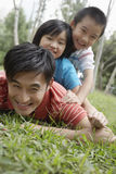 Playful Father With Children Lying On Grass Stock Photos
