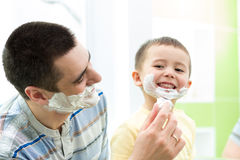 Playful father and his son having fun in bathroom Royalty Free Stock Image