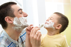 Playful father and his son shaving in bathroom. Playful father and his son shaving and having fun in bathroom Royalty Free Stock Images