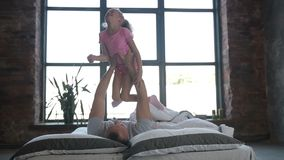 Playful father lifting his daughter on bed at home stock video