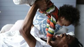 Playful father lifting son up while lying on bed stock footage