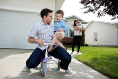 Playful Father Sitting on Tricycle With Son. While wife standing in background with daughter royalty free stock photo