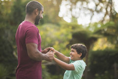 Playful father and son enjoying at park royalty free stock photography